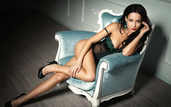 attractive-sex-worker-with-dark-hair-sits-provocatively-on-couch-in-lingerie | Garden of Eden Brothel Melbourne